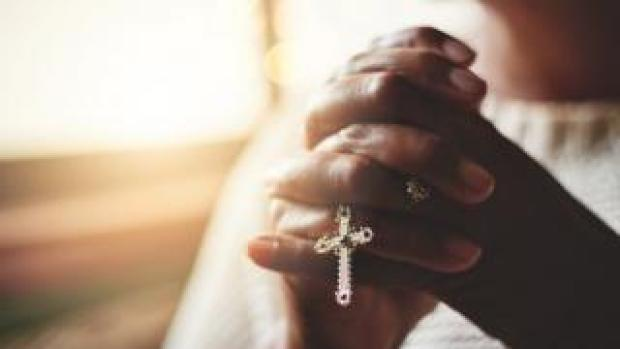 Closeup shot of an unrecognizable woman holding a rosary while praying
