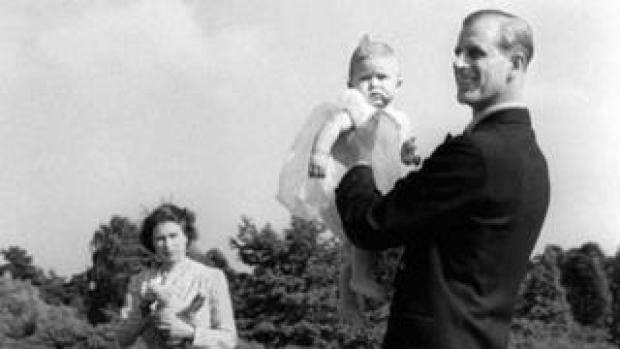 Prince Charles, later The Prince of Wales, is lifted up by his father The Duke of Edinburgh, in the grounds of Windlesham Moor, the country home in Surrey of Princess Elizabeth and the Duke. 18 July 1949