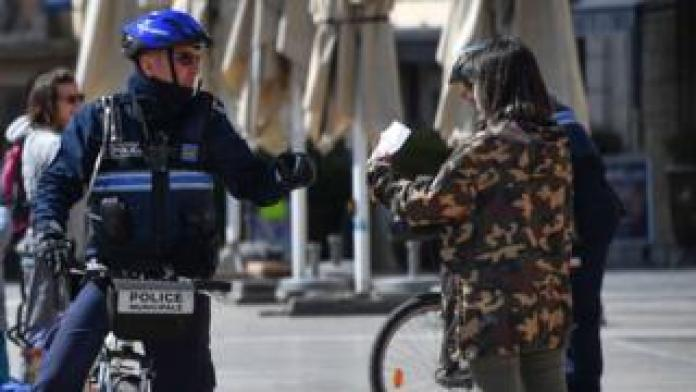 A municipal police officer checks a passerby for his certificate while they monitor the movements of people in Montpellier, March 25, 2020