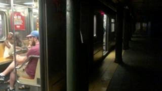 Train at darkened platform at 66th Street subway station in Manhattan, NY, 13 July 2019