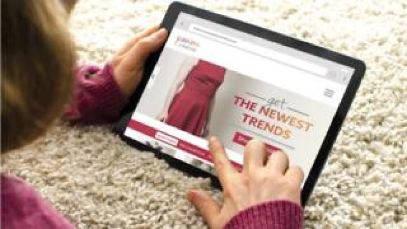 Woman looking at fashion ad on tablet