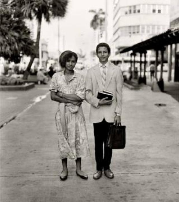 A well-dressed couple pose of the camera