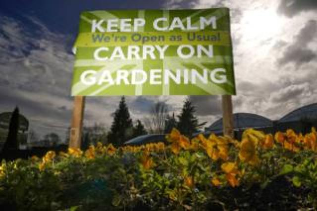 """A sign tells people to """"Keep calm and carry on gardening"""""""