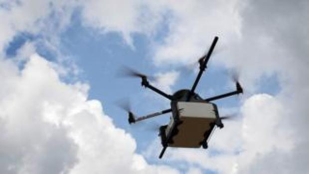 A drone carrying a parcel is seen in the sky