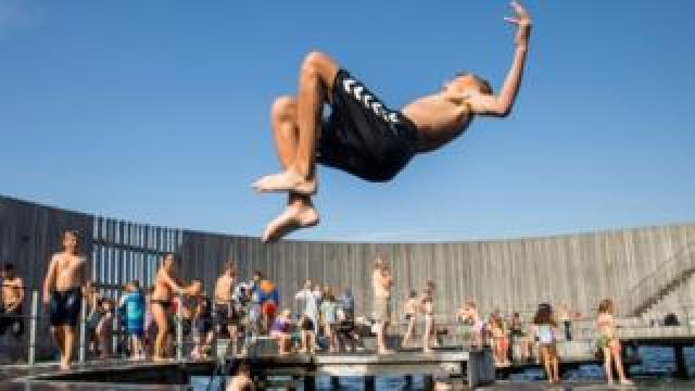 Boys jump in the water at the Snail on Amager in Copenhagen, Denmark June 25, 2019.