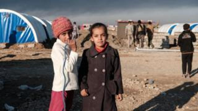 Two girls look at the camera amid a refugee camp with the blue tents of UNICEF visible nearby