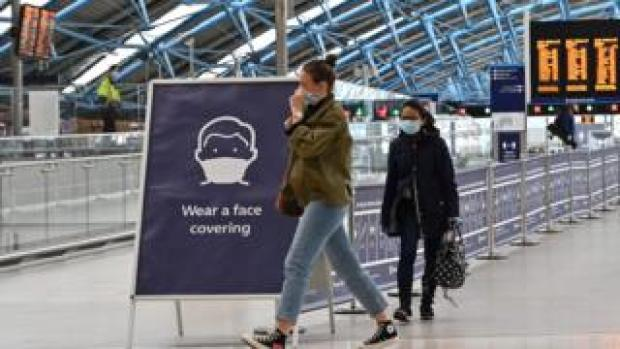 "A sign tells passengers to ""wear a face covering"" at Waterloo train station in central London , on June 8, 2020, as the UK government's planned 14-day quarantine for international arrivals to limit the spread of the novel coronavirus COVID-19 begins."