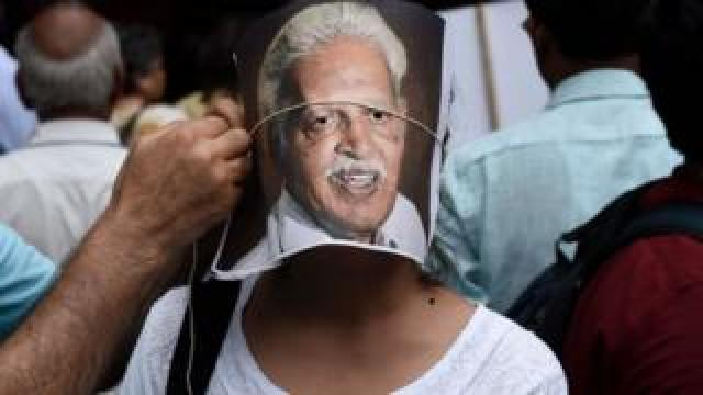 A protester adjusts a portrait of poet Varavara Rao on the face of another protester during a demonstration against the arrests of civil and democratic rights activists by the Maharashtra Police, at Parliament Street, on August 30, 2018 in New Delhi, India