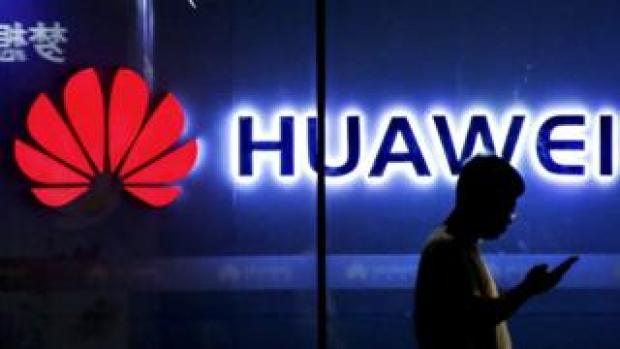 Man walks in front of Huawei sign