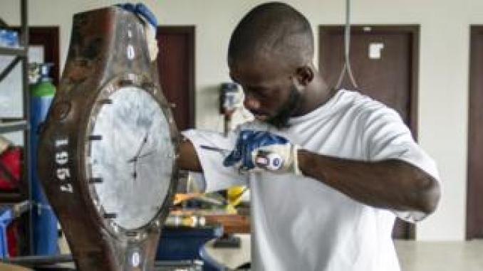 A Ghanaian artist making a clock