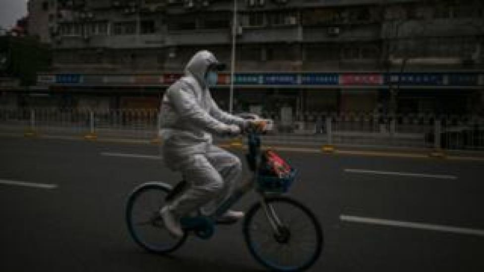 A man rides a bike around the streets of Wuhan