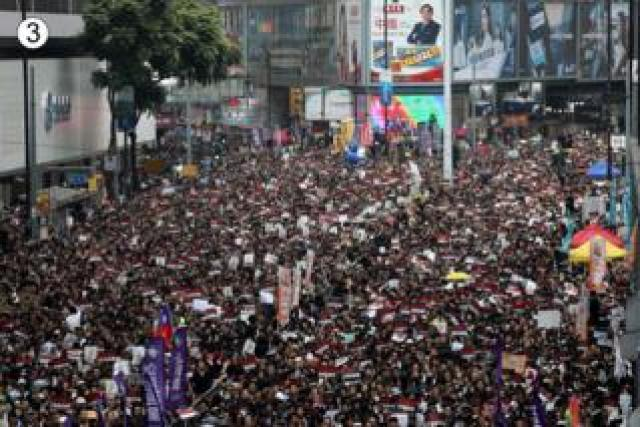 The Sogo deparment store, left, can be seen amid the huge crowd as the road parts in a V shape behind them