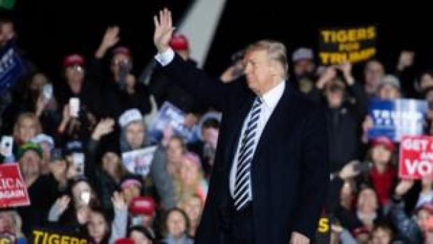 US President Donald Trump waves to supporters during a campaign rally at Columbia Regional Airport in Columbia, Missouri