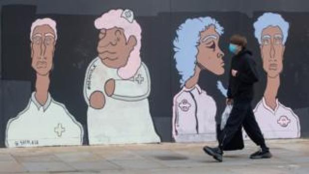 A man wearing a mask walks past a mural of BAME medical and transport workers