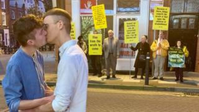 Joe Fergus and Robert Brookes kissing in front of protesters