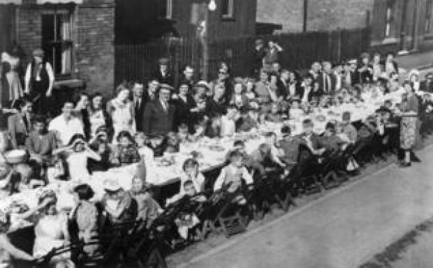 A VE Day celebration street party with people having a meal at a long table