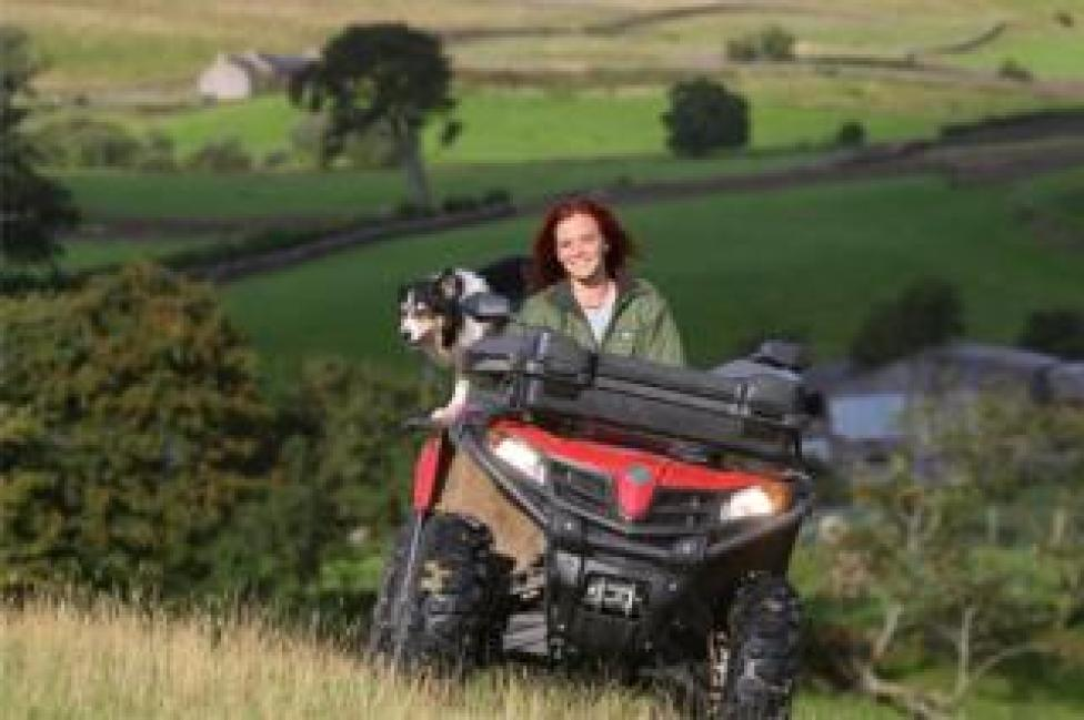 Hannah Jackson on her quad bike with her dog