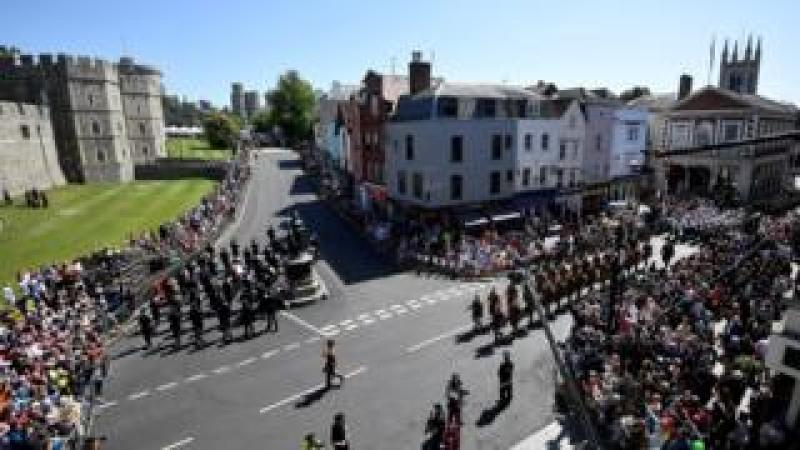 Police officers and members of the public watch as military personnel rehearse their part in the procession