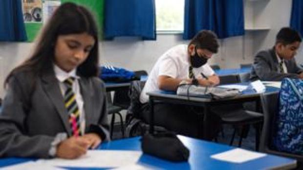 A pupil wears a face covering in a school classroom in Leicester