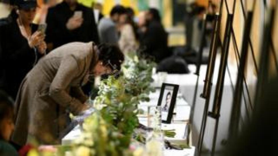 A woman writes in a memorial book at a service for victims of the plane crash in Edmonton, Canada