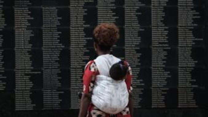 Woman looking at list of Rwanda genocide victims