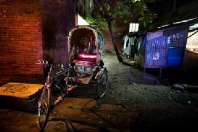 A bicycle rickshaw in a dimly lit back street in Bangladesh. F M Hall Rickshaw. Part of 'Crossfire', a photo story by Shahidul Alam.