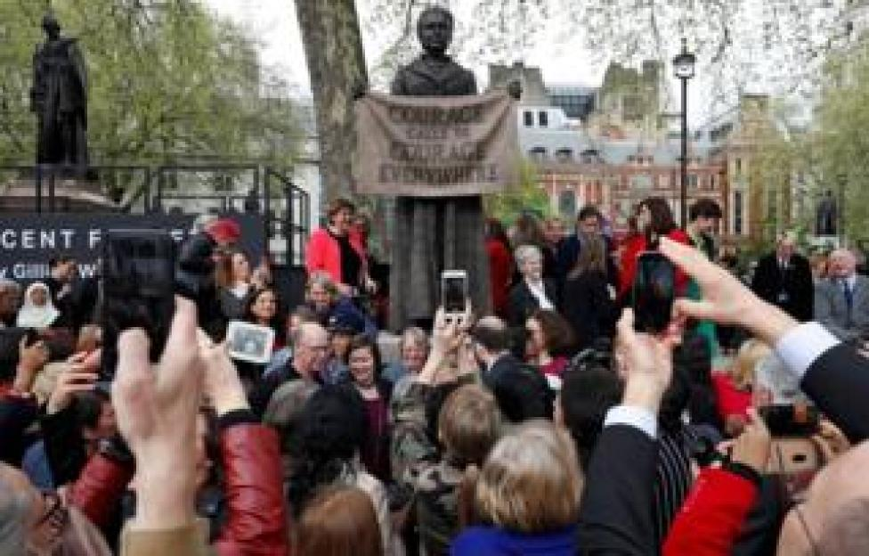 People pose for photographs with a statue of suffragist and women's rights campaigner Millicent Fawcett