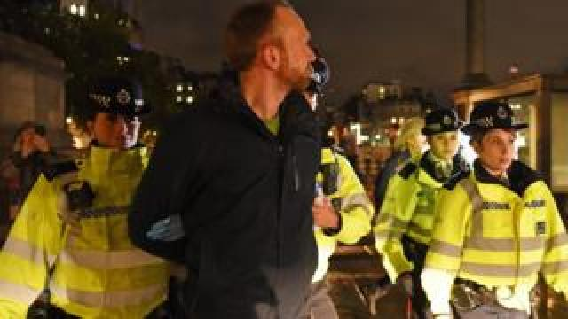 Police remove an Extinction Rebellion protester from Trafalgar Square in central London