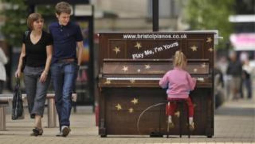 A girl plays a piano installed in Bristol's Broadmead in 2009