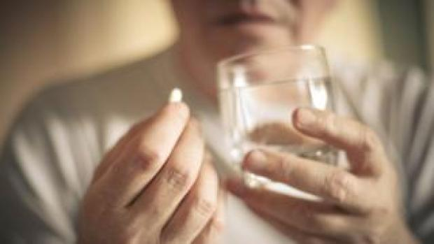 A woman holds a painkiller pill and a glass of water