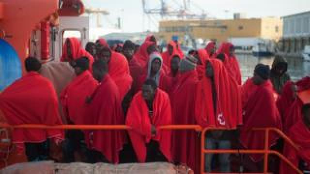 Migrants are seen standing on a rescue boat as they wait to disembark after their arrival at the Port of Malaga, Spain