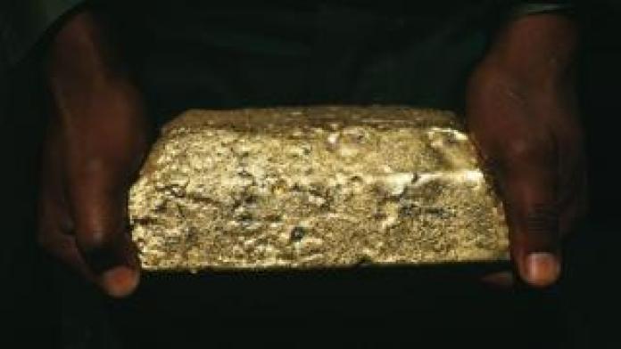 A man holds a gold ingot