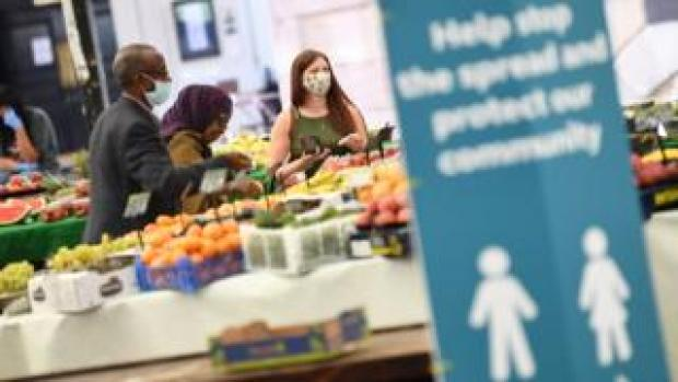 People wearing face masks as they shop at an open fruit and vegetable market in Leicester
