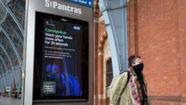 A woman leaving St Pancras International station wearing a mask