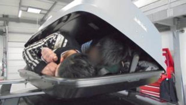 The three people lying inside the roof box