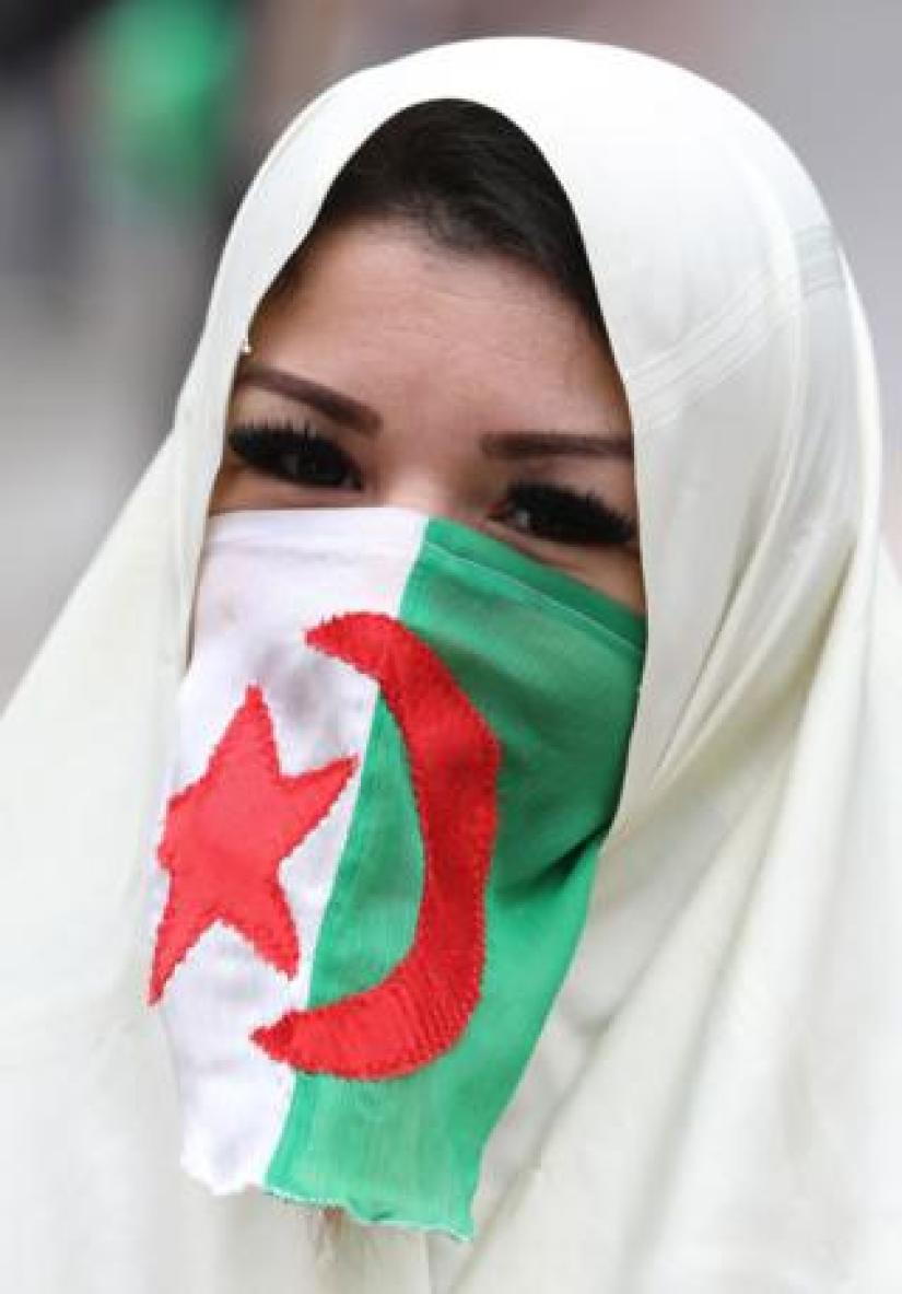 A woman in a hijab and an Algerian flag covering her nose and mouth