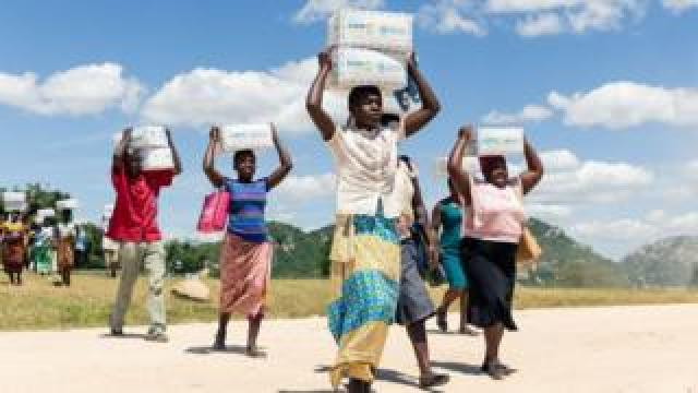 Women carry boxes of porridge for their children, on March 13, 2019, in the Mutoko rural area of Zimbabwe
