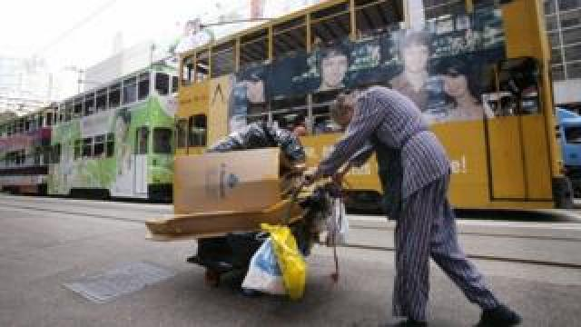 An elderly woman collecting rubbish