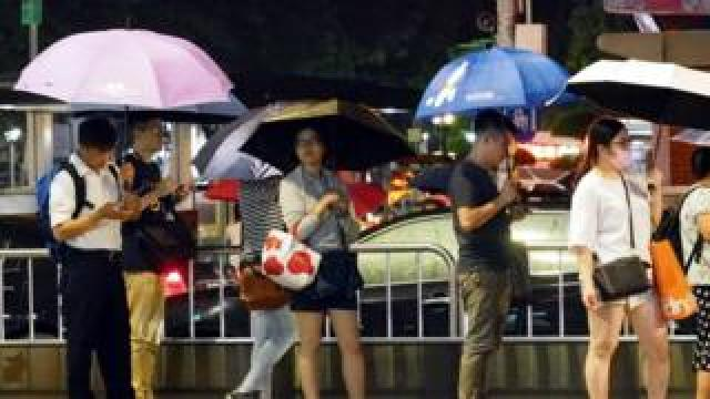 People wait at a bus stop during a shower brought by Typhoon Lekima in Taipei, Taiwan, 08 August 2019