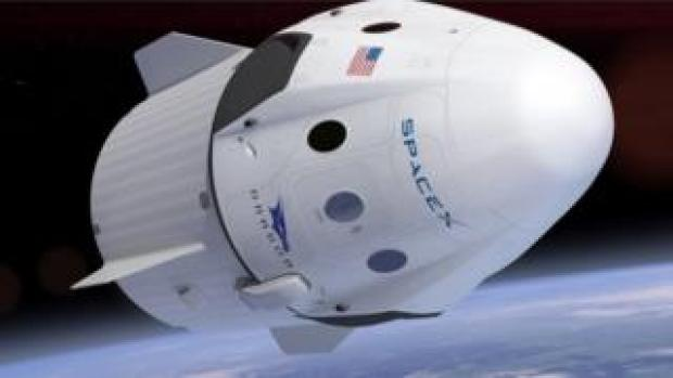 A rendition of Crew Dragon's capsule flying above Earth