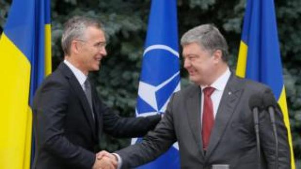 Ukrainian President Petro Poroshenko and Jens Stoltenberg, the Secretary General of nATO, shake hands after a joint news conference following their meeting in Kiev