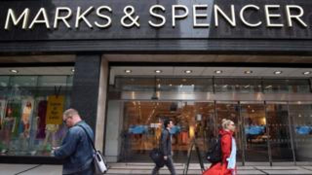 People walking past Marks and Spencer store