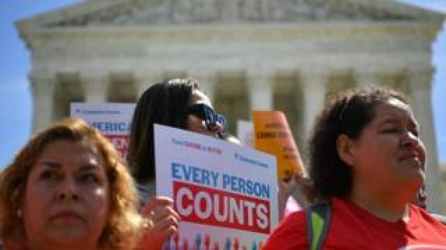 """Three protestors outside the White House on 23 April. One holds up a sign saying """"Every person counts""""."""