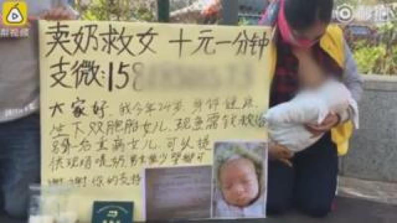 Woman kneels on street in China, breastfeeding a baby. The sign beside her has a picture of her ill baby and writing in Chinese characters. There are two plastic bags apparently filled with breast milk in the foreground.