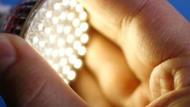 Man holding LED light bulb