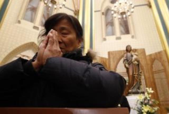 A woman prays at the Xishiku Catholic Church in Beijing, China