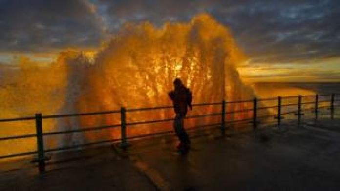 Man with waves at sunrise