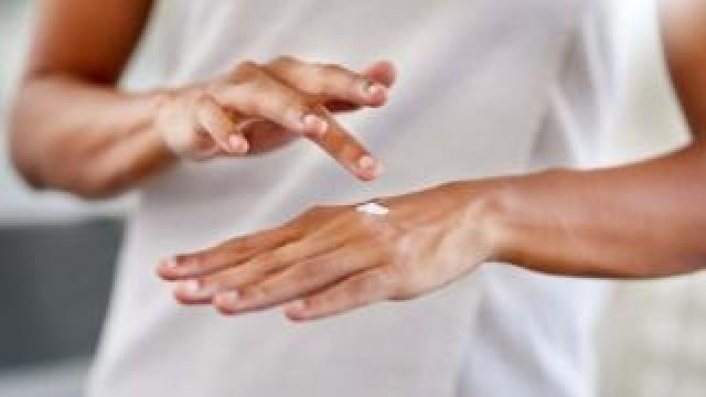 Woman putting cream on her hand