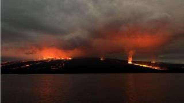 Handout picture released by the Galapagos National Park press service showing lava flowing down the Sierra Negra volcano on Isabela Island in the Galapagos Archipelago about 1000 km off the Ecuadorean coast in the Pacific Ocean, early on June 27, 2018.