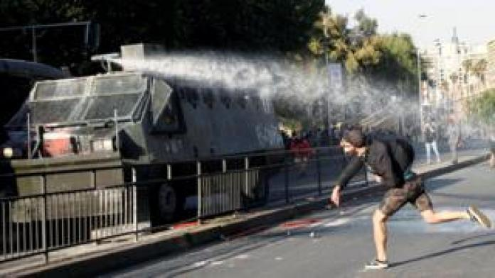 A demonstrator clashes with riot police during a protest against the increase in the subway ticket prices in Santiago